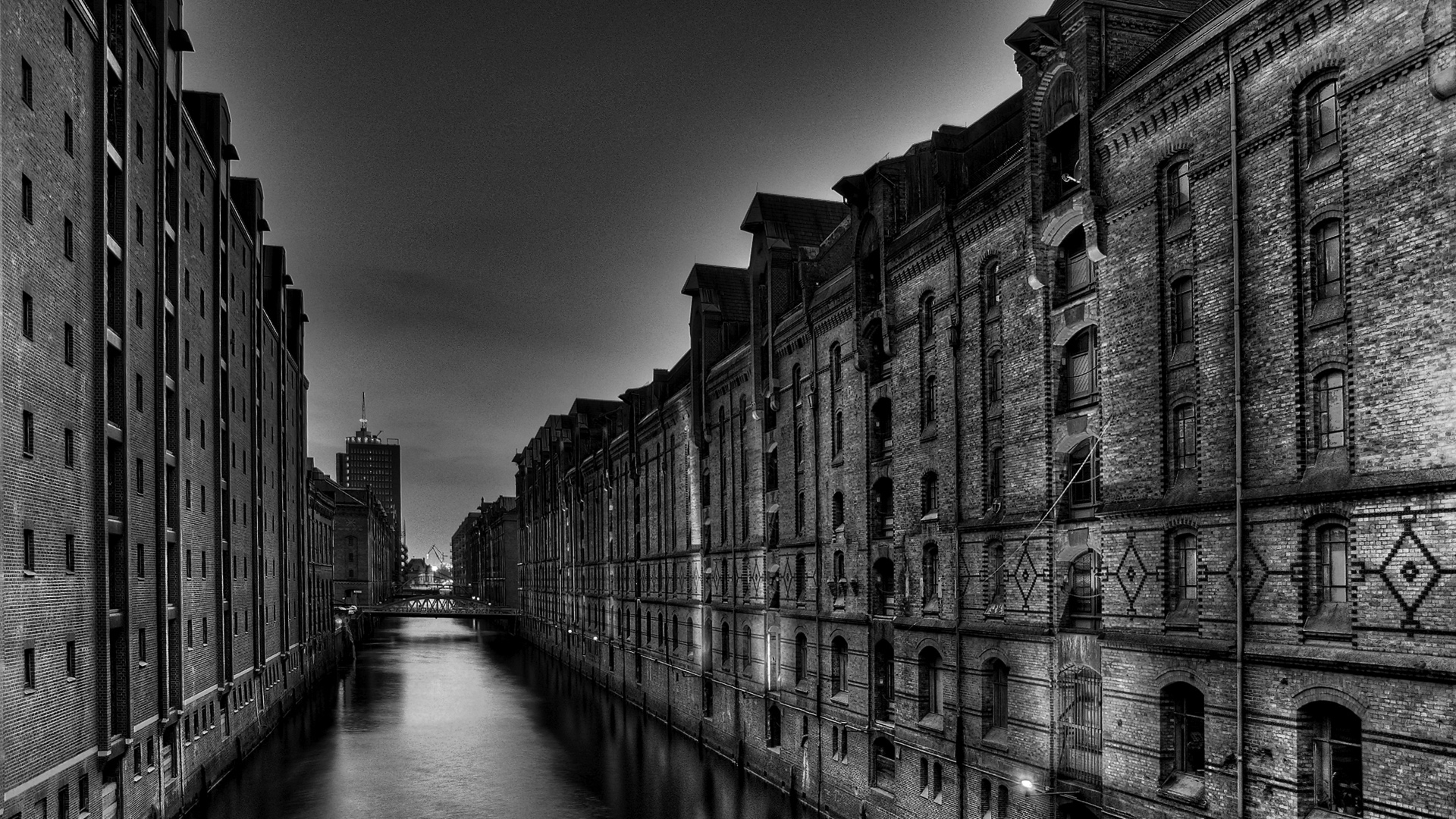 black and white photograph of old city by canal